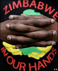 Protestor grips his hands in front of his t-shirt during a weekly protest against the Mugabe leadership in Zimbabwe