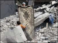Children remove a carpet from rubble in south Lebanon