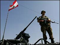 A Lebanese soldier stands next to a Lebanese fla
