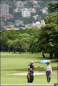 A golfer and caddy at Caracas Country Club