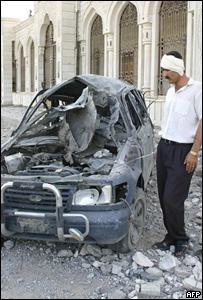 Iraqui herido observa un veh�culo usado como carro bomba
