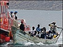 Barco guardacostas español junto a un cayuco africano
