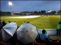 Spectators huddle under umbrellas