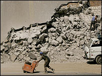 Workers clear rubble from a Lebanese bridge destroyed by Israel