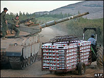 A farmer in a tractor passes an Israeli tank in Lebanon