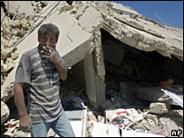 Man stands near his destroyed house in Qana, Lebanon