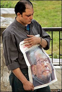Mourner holds a newspaper front page showing Naguib Mahfouz