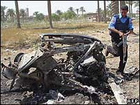 An Iraqi policeman inspects a destroyed vehicle used as a car bomb