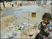 Palestinian girl stands near open sewage
