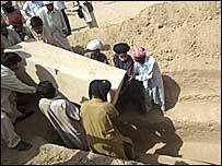 Coffin is placed in the grave at funeral in Dera Bugti