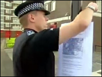 A police officer posts a dispersal order notice