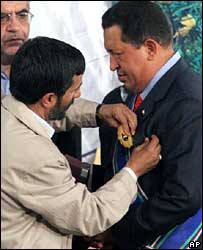 Iran's President Mahmoud Ahmadinejad pins a ceremonial award to Hugo Chavez's jacket in Tehran