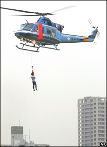 A Tokyo police helicopter pulls a man from a river