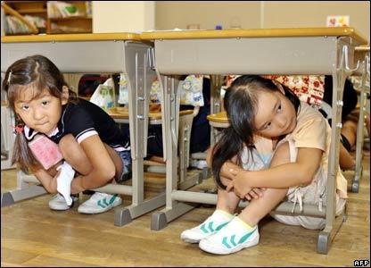 Primary school children crouch under their desks at a school in Tokyo