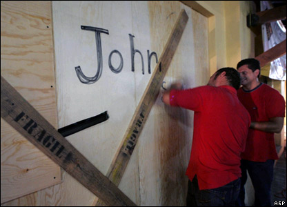 Residents of Cabo San Lucas, Mexico, reinforce the door of a house.
