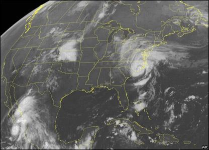 A satellite image showing Hurricane John poised just south of the Baja California peninsula and Ernesto off the Carolinas.