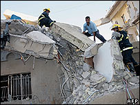 Firefighters search rubble of destroyed building in Baghdad