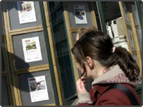 A girl looks into an estate agent's window