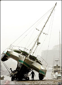 A man walks under a tri-hull sailboat leaning halfway off its trailer in Cabo San Lucas, Mexico