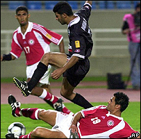Iraq's Qahtan Chatir jumps over a tackle by Lebanon's Mohammed al-Reda in an Asian Cup match