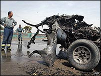 Afghan police officers look at the wreckage of car used in the suicide attack