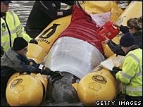 Rescuers attempt to transport the whale to deeper waters