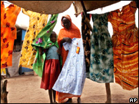 A Sudanese woman buys a dress for her daughter at the Zamzam refugee camp, south of Al-Fasher, Sudan.