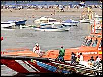 Un barco de inmigrantes arriba a la costa, custodiado por la policía.