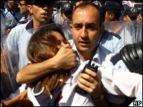 A policeman detains a protester near the parliament in Ankara, Turkey
