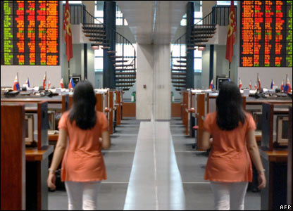 A broker is mirrored in the glass of the Philippine Stock Exchange in Manila
