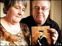 Norma and Rod Stokes holding photo of their son, Christopher
