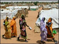 Sudanese women walk at the Riyad refugee camp