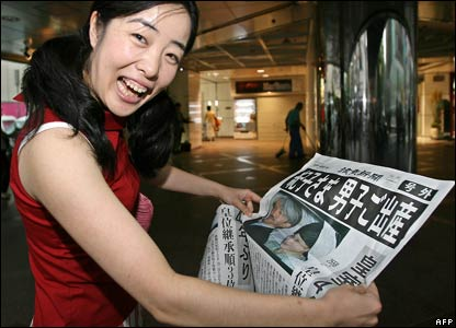 A woman smiles as she reads a special edition of the newspaper announcing the birth