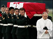 Pallbearers carry coffin