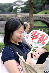 """A young woman carries a baby holding a paper fan saying """"celebration"""" in front of the imperial palace in Tokyo"""
