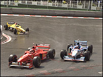Michael Schumacher passes Jean Alesi's Benetton, with Giancarlo Fisichella's Jordan behind, on his way to victory in the 1997 Belgian Grand Prix