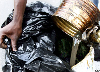An Ivorian man pours toxic waste into a tank