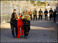 US military police escort detainee at Guantanamo Bay