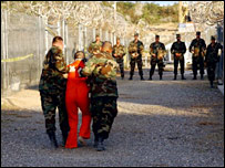 US military police escort detainee at Guantanamo Bay