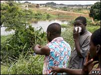 People look at a site where toxic waste was dumped in Abidjan