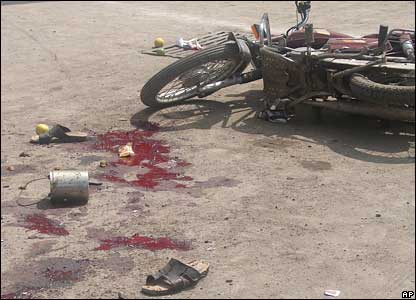 An abandoned motorcycle, blood stains and a pair of sandals on the street of Malegaon after the blasts