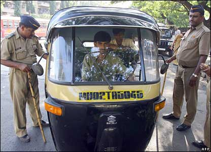 Police check the papers of an auto-rickshaw passenger in Mumbai