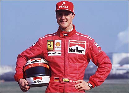 Michael Schumacher poses in his new Ferrari overalls