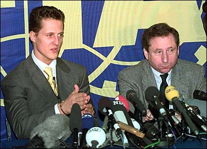 Michael Schumacher and Ferrari team boss Jean Todt speak at a news conference following the decision to strike his points from the 1997 record