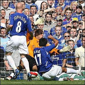 Tim Cahill scores the opening goal past Jose Reina at Goodison Park