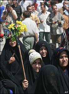 Women carry flowers in Karbala