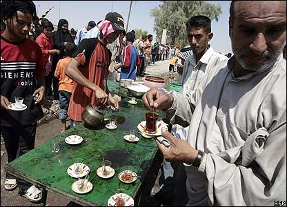 People take tea from a street stall in Karbala