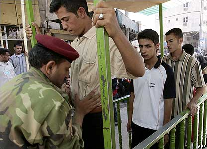 Iraqi soldiers frisk pilgrims entering a mosque in Karbala