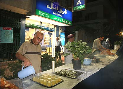 A man pours drinks outside his shop
