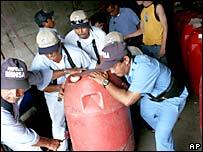 Policías cargan un bote con alcohol adulterado en Nicaragua